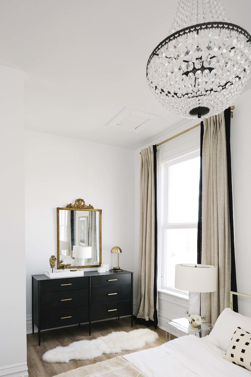 Neutral bedroom with black wide dresser and crystal chandelier via Shelby Girard