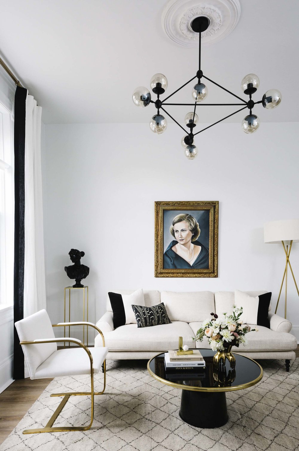 Neutral sofa with black and gold coffee table living room via Shelby Girard