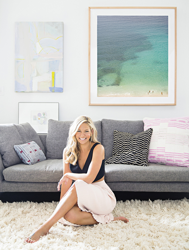Sally King Benedict in her Atlanta home with grey couch and ocean artwork