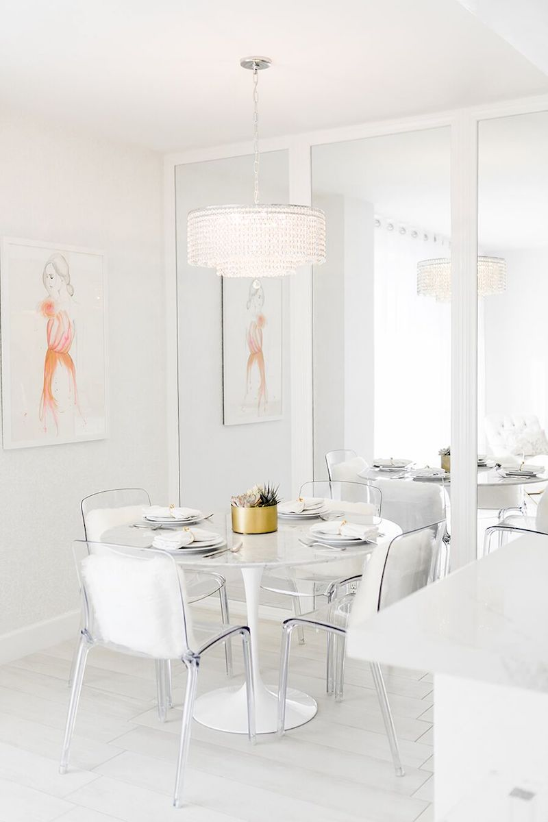 White dining room with crystal chandelier and marble tulip table via Sydne Summer