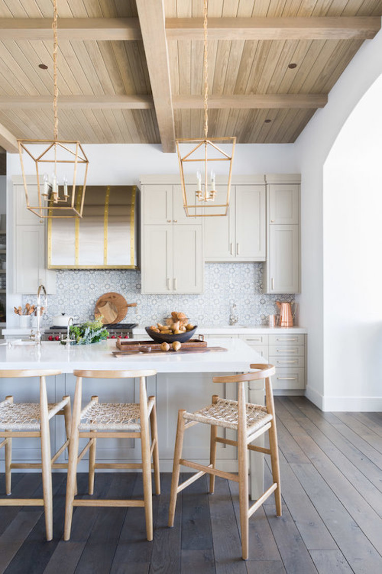 White kitchen with cage lighting and wood panel ceilings by Nicole Davis