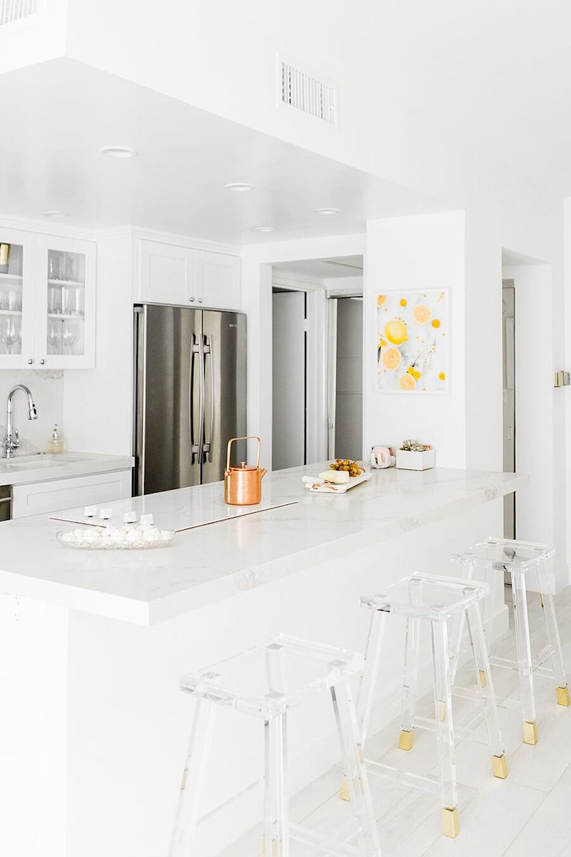 White marble kitchen with stainless steel fridge and lucite bar stools via Sydne Summer