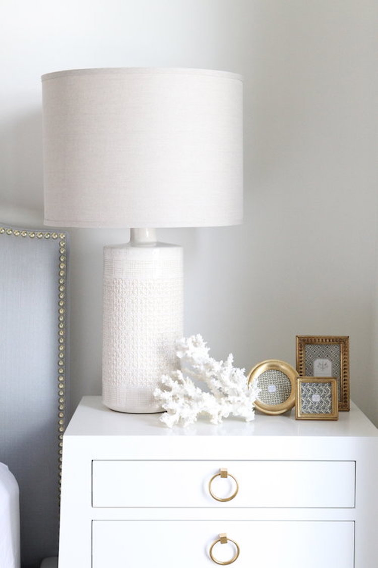 White nightstand with gold ring pulls and white table lamp design by Nicole Davis