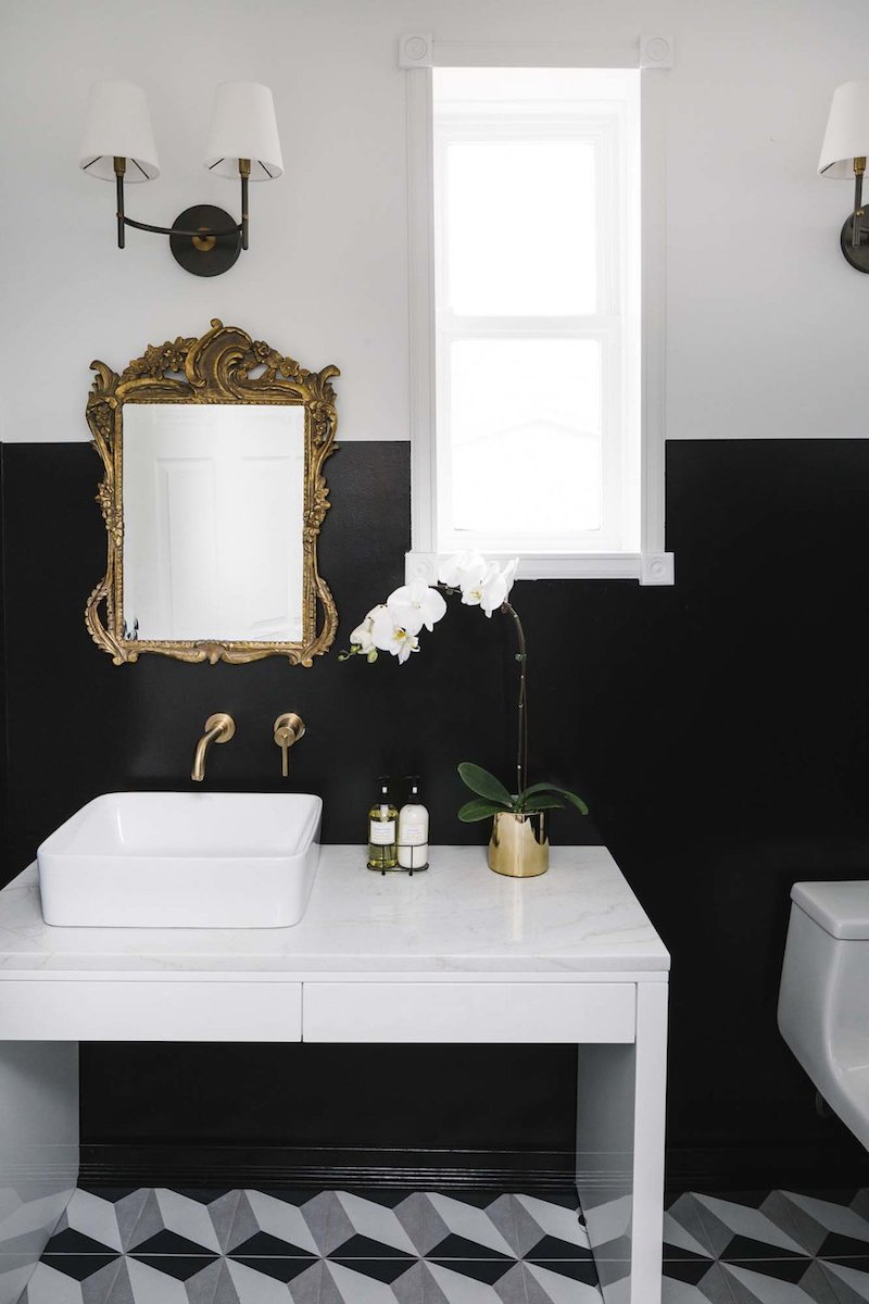 White vessel sink with brass faucet, antique gold mirror and black walls