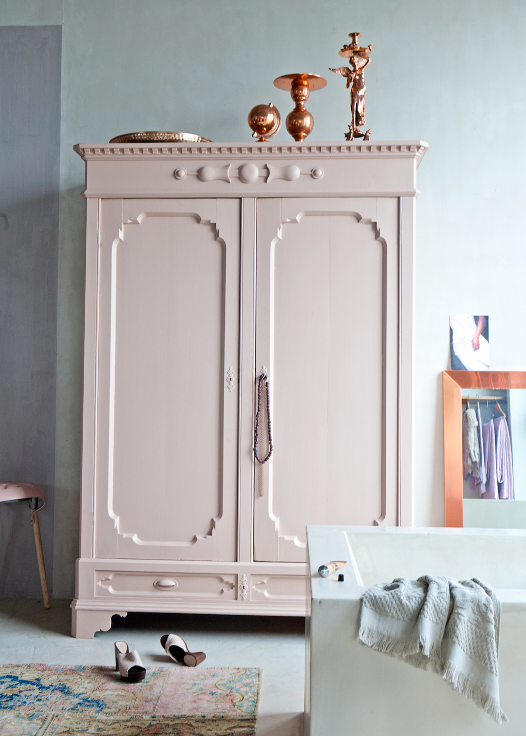 Soft pink armoire with copper decor accents