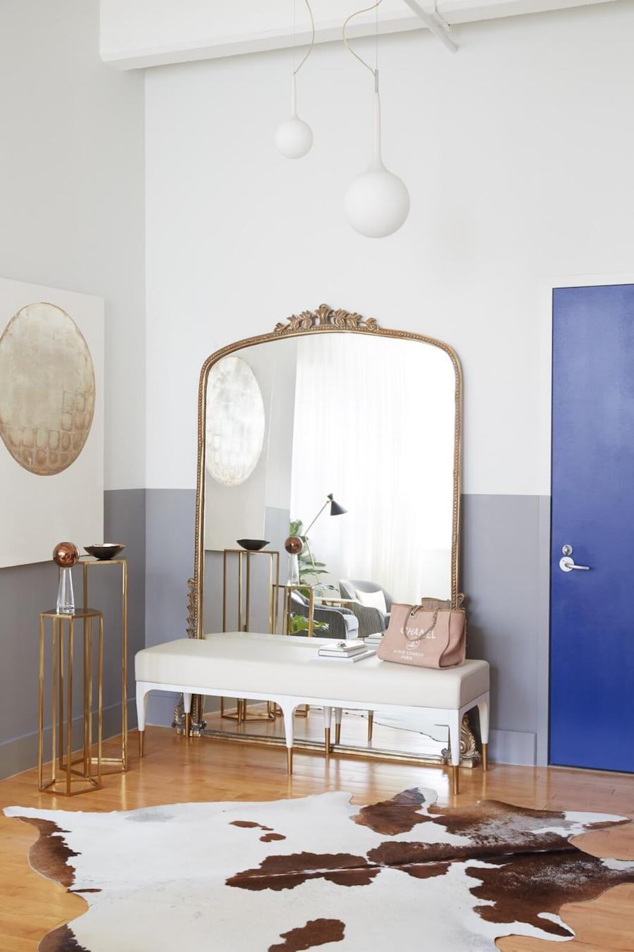 Anthropologie Gleaming Primrose Mirror on floor in Brooklyn loft with white bench and cowhide rug