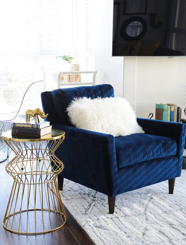 Blue velvet tufted accent chair with white throw pillow