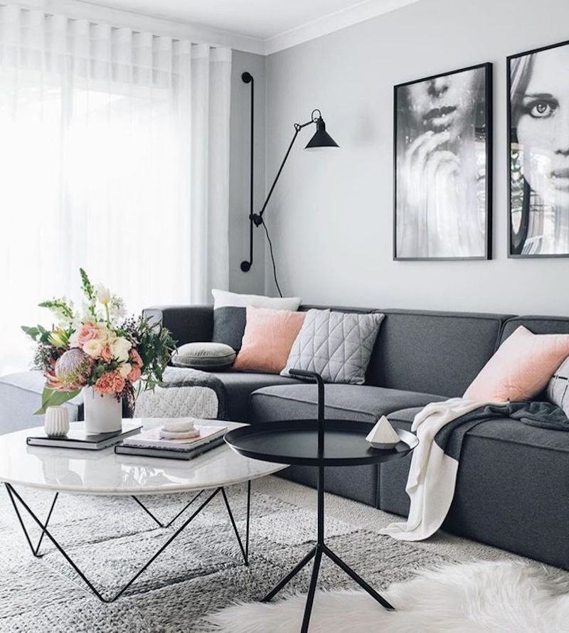 Dark grey sofa with marble coffee table and dramatic art