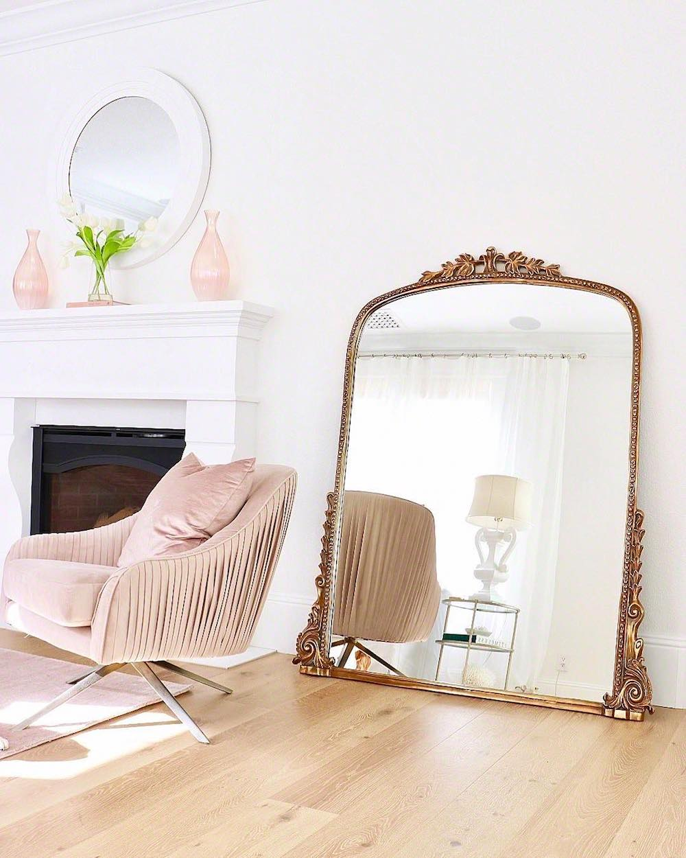 Gold 7-foot Gleaming Primrose Mirror with blush velvet chair in living room