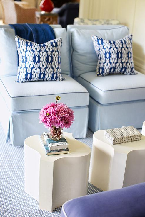 Light blue slip cover accent chairs with cream side tables and patterned throw pillows