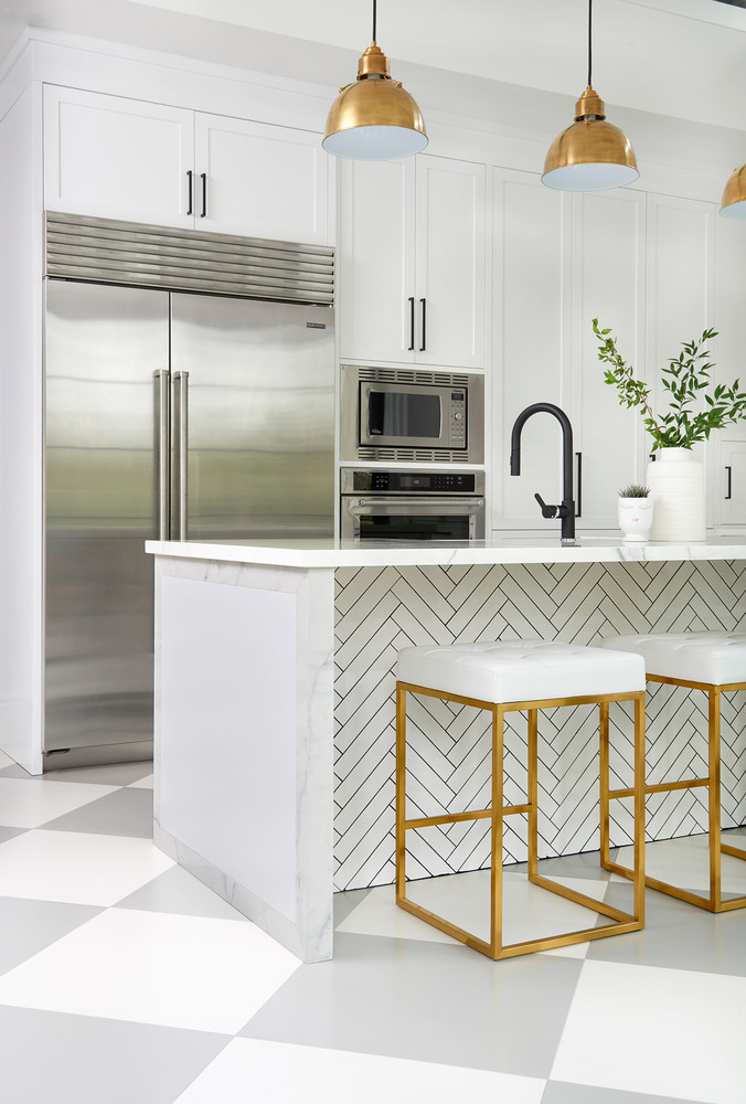 Stainless Steel Fridge In White Marble Kitchen With Brass Lighting