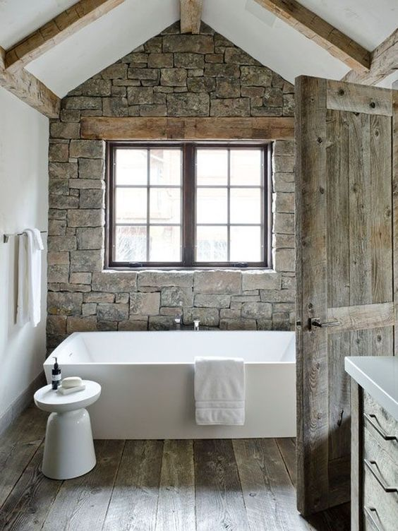 Rustic Stone Wall Bathroom With Wood Panel Flooring And Wooden Door