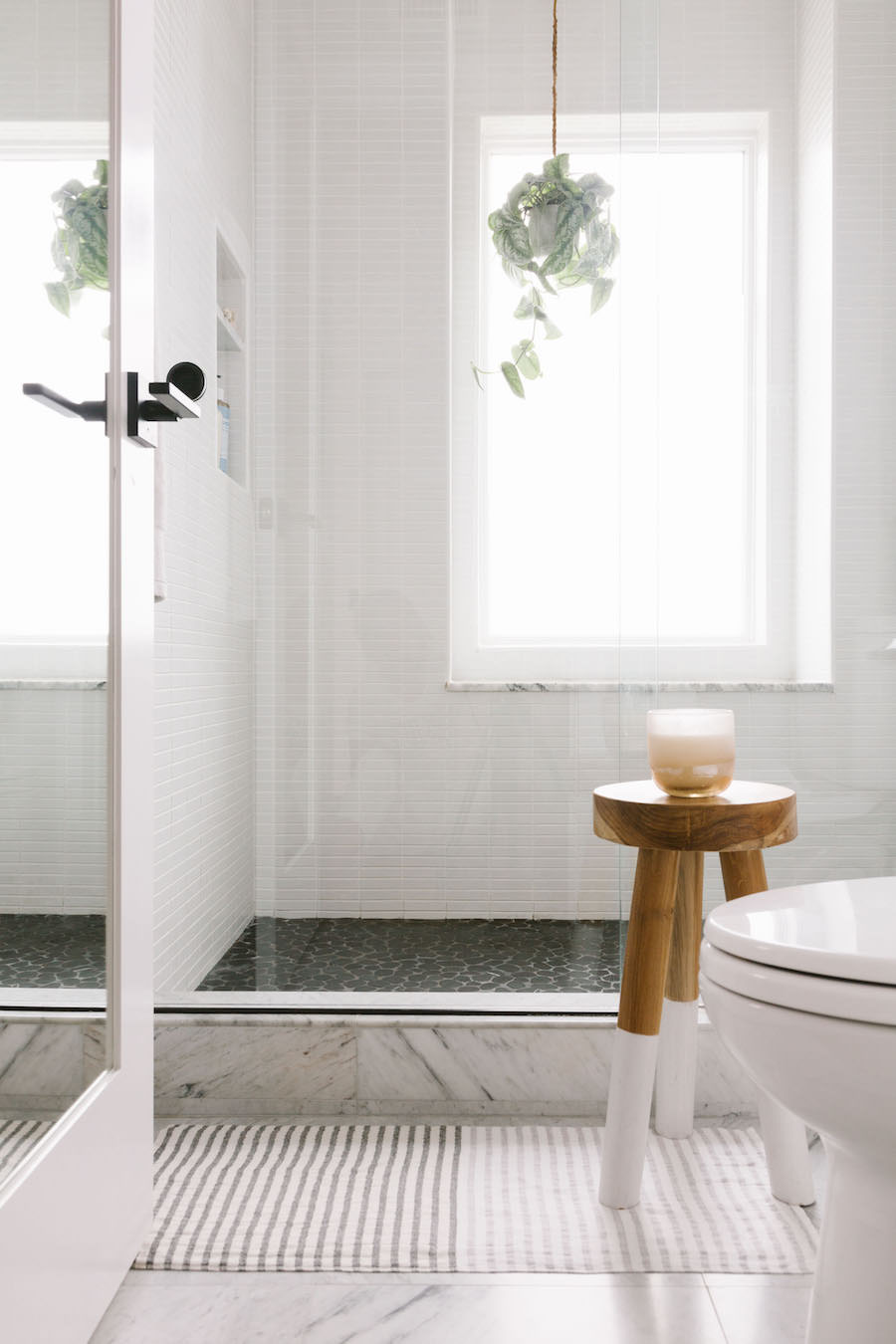 White Shower With Hanging Plant And Grey Floor Tile Bathroom
