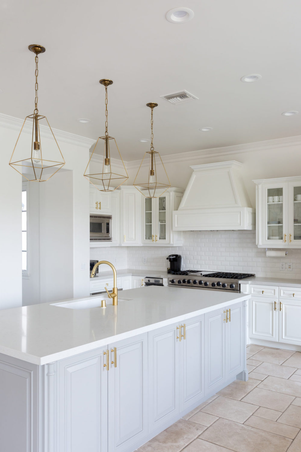 Brass Cage Lights In Kitchen With White Subway Tiling