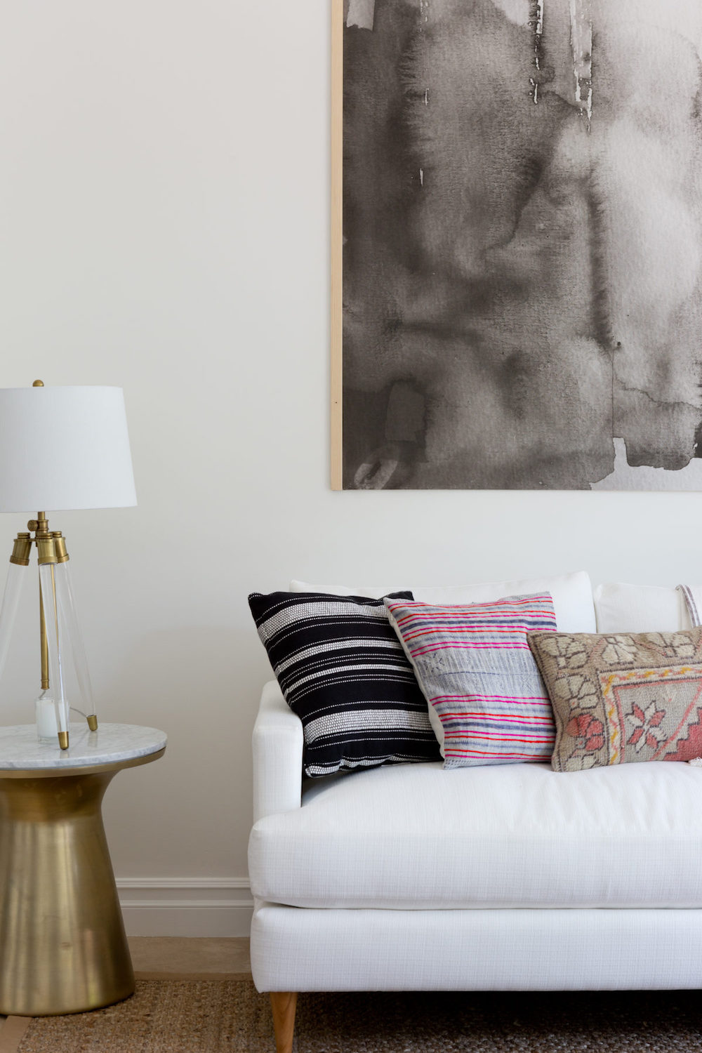 White Sofa With Colorful Throw Pillows And Brass Marble Side Table