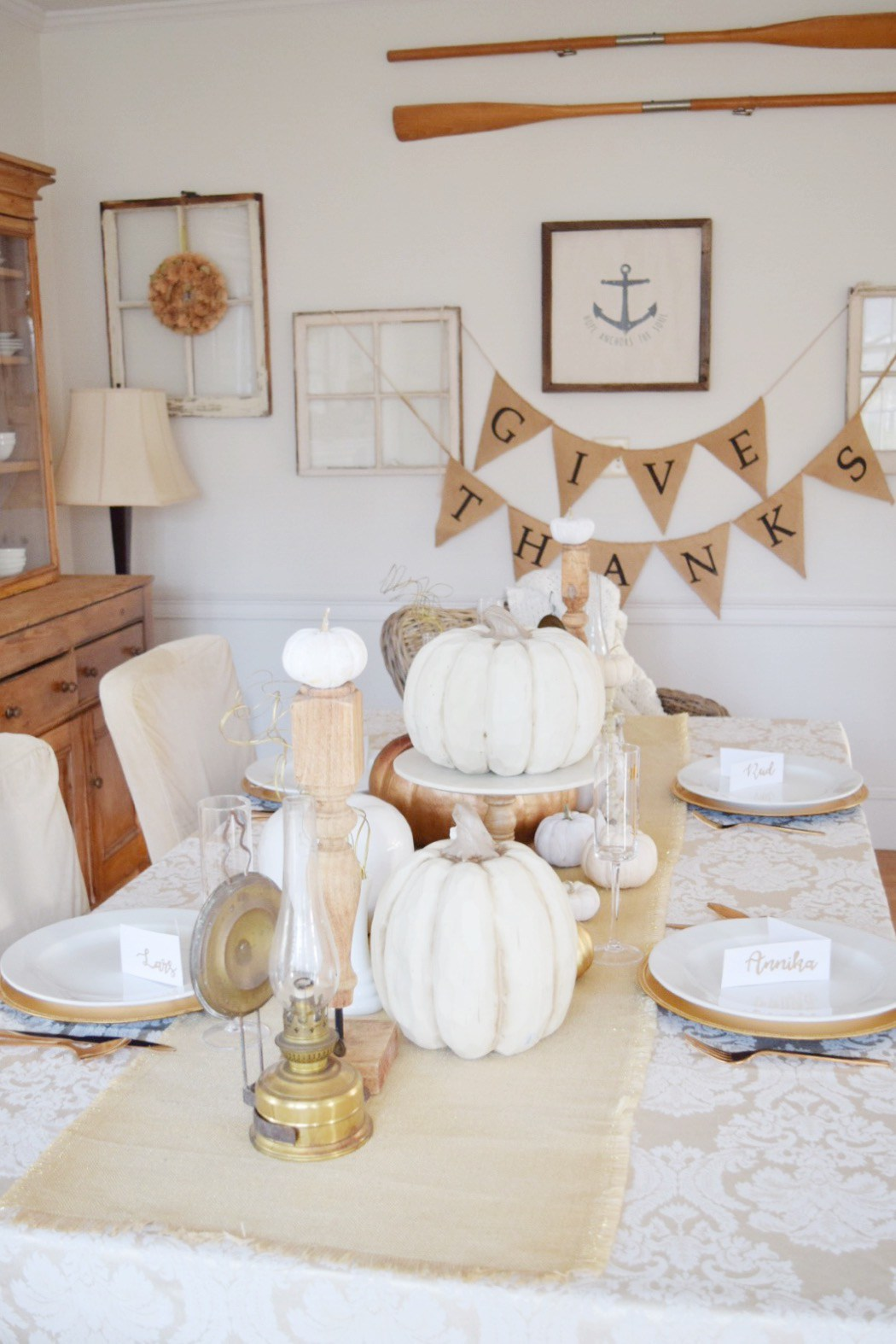Thanksgiving Tablescapes With Large White Pumpkins And Give Thanks Paper Banner Via Gratefully Vintage