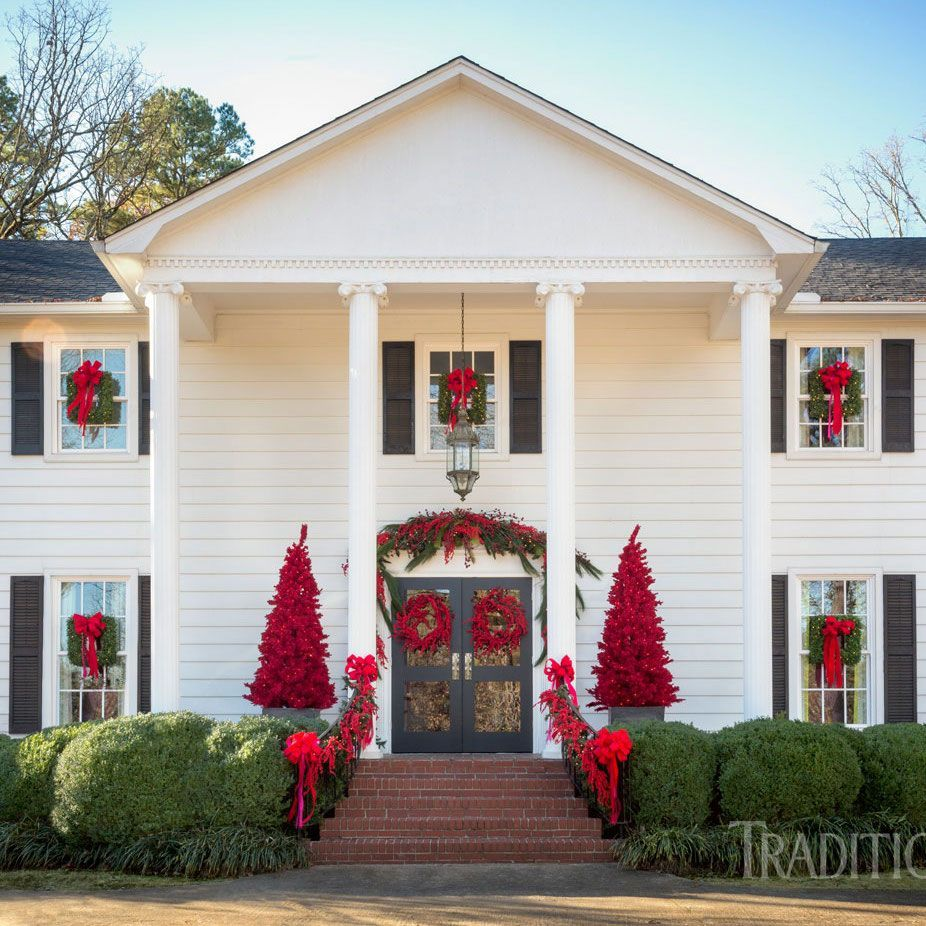 Christmas House Decor - Red Trees and Wreaths on a Colonial Home via Traditional Home