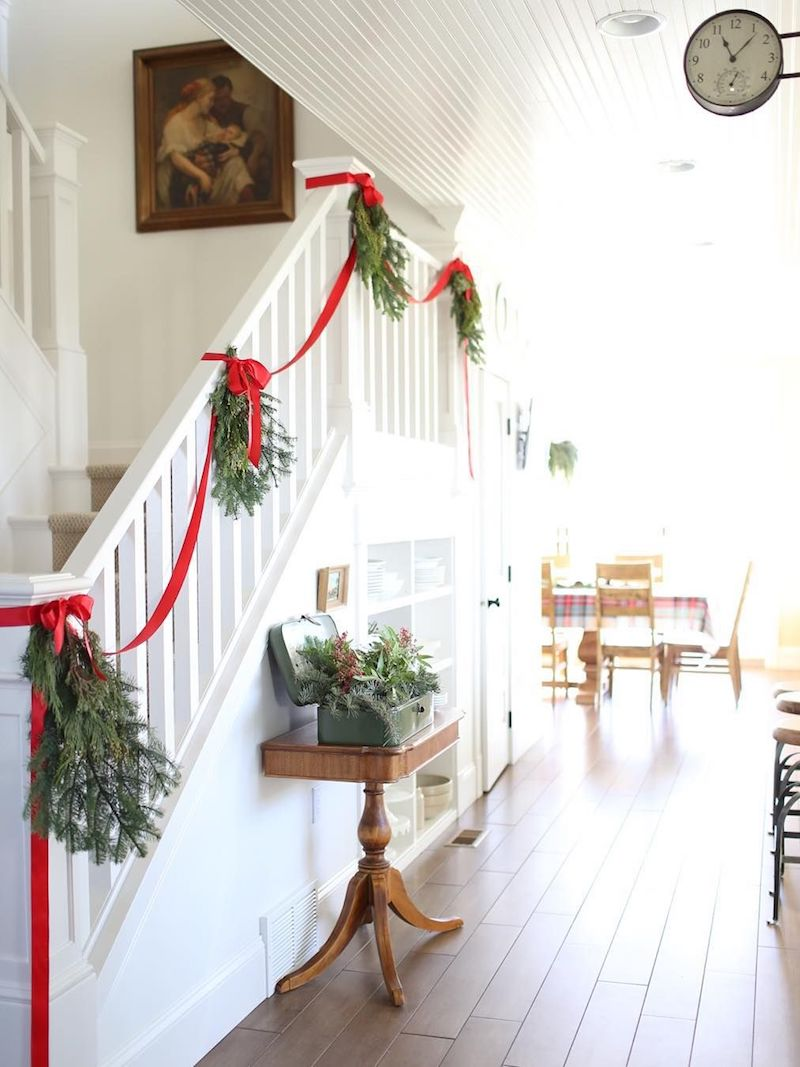 Green Wreaths with Simple Red Ribbon Staircase Decor via @thefarmchicks