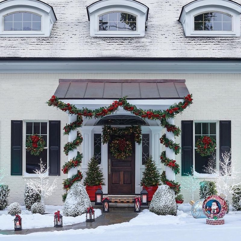 Wrapped garlands and red ribbons at the front door of this Christms house via frontgate 3