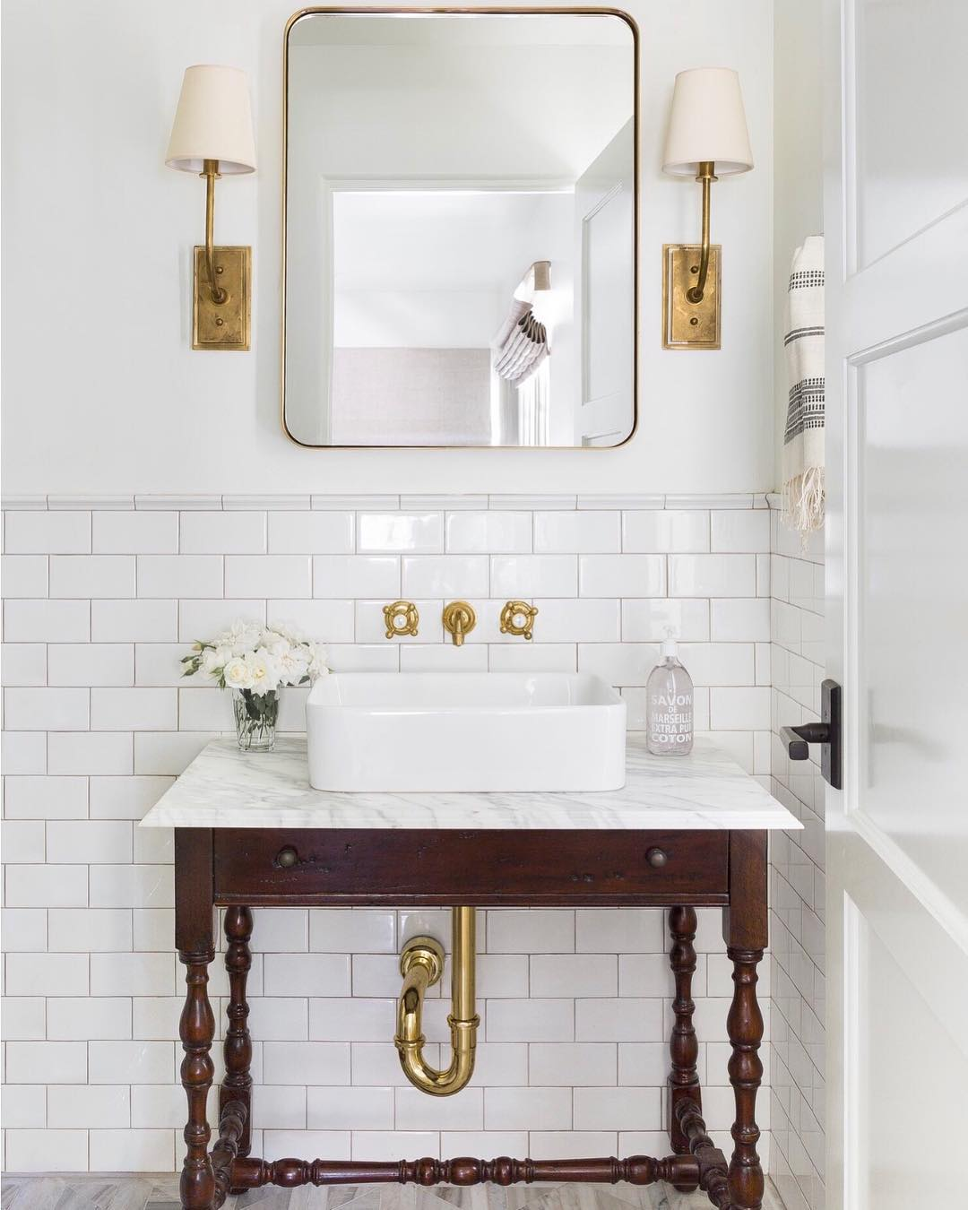 Bathroom with subway tile, vessel sink and brass hardware
