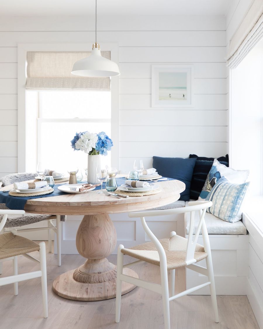 Beach home breakfast nook with wishbone chairs, shiplap walls and round dining table