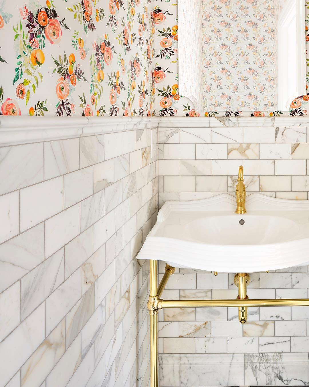 Brass bathroom washstand with marble subway tile