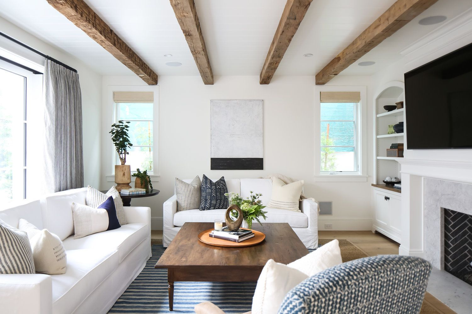 Coastal living room with white sofas and wood coffee table by Kelly Nutt