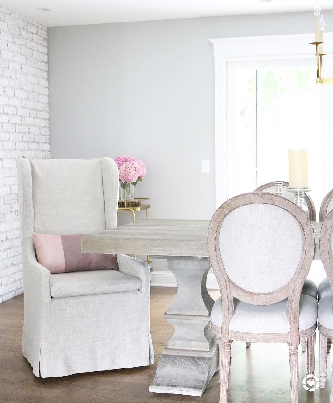 Feminine farmhouse dining room with french dining chairs and slipcover chair