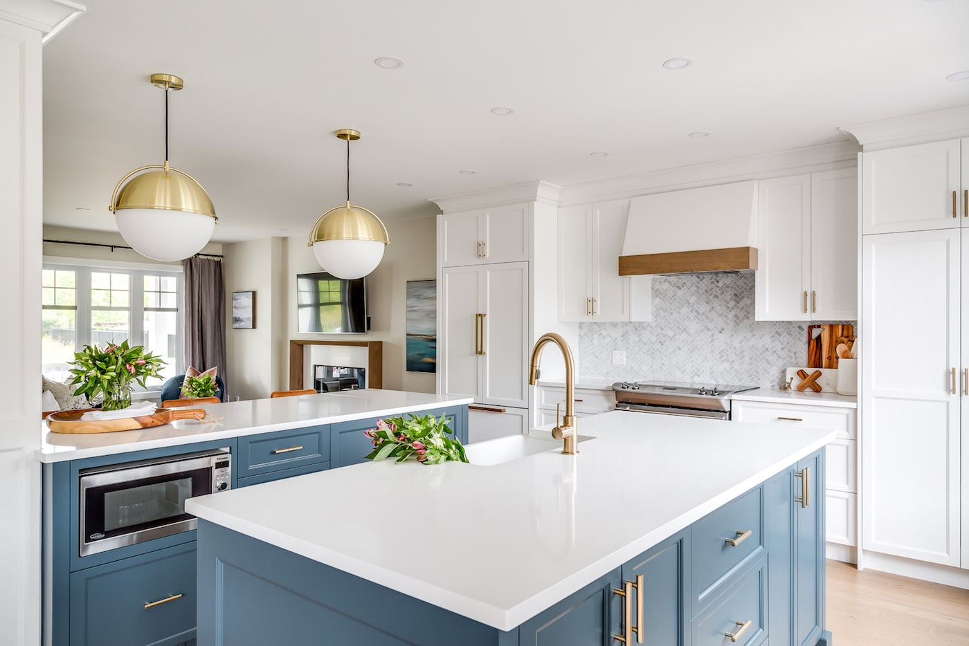 Kitchen with turquoise cabinets and brass pendant lights