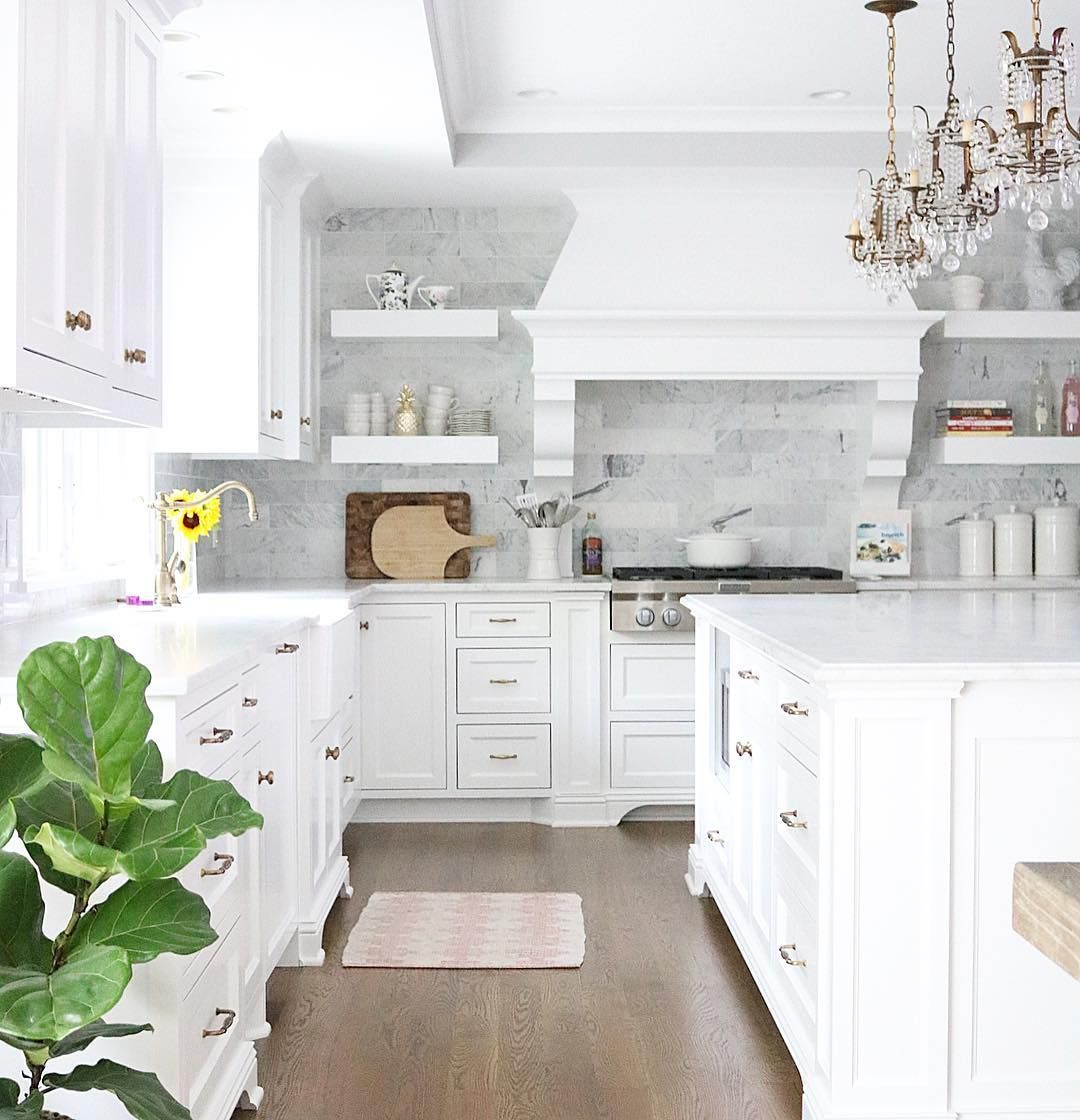 White kitchen with crystal chandelier pendants and marble subway tile