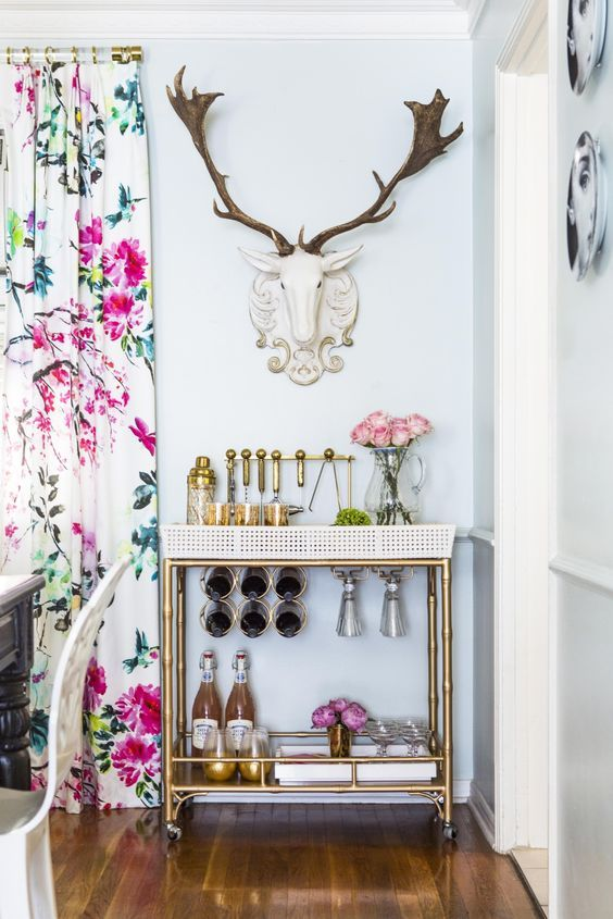 Brass bar cart and floral curtains