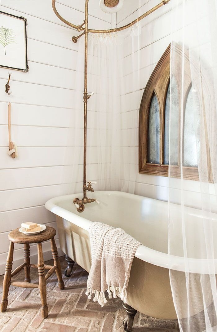 Brass shower hardware and wooden stool in Country bathroom