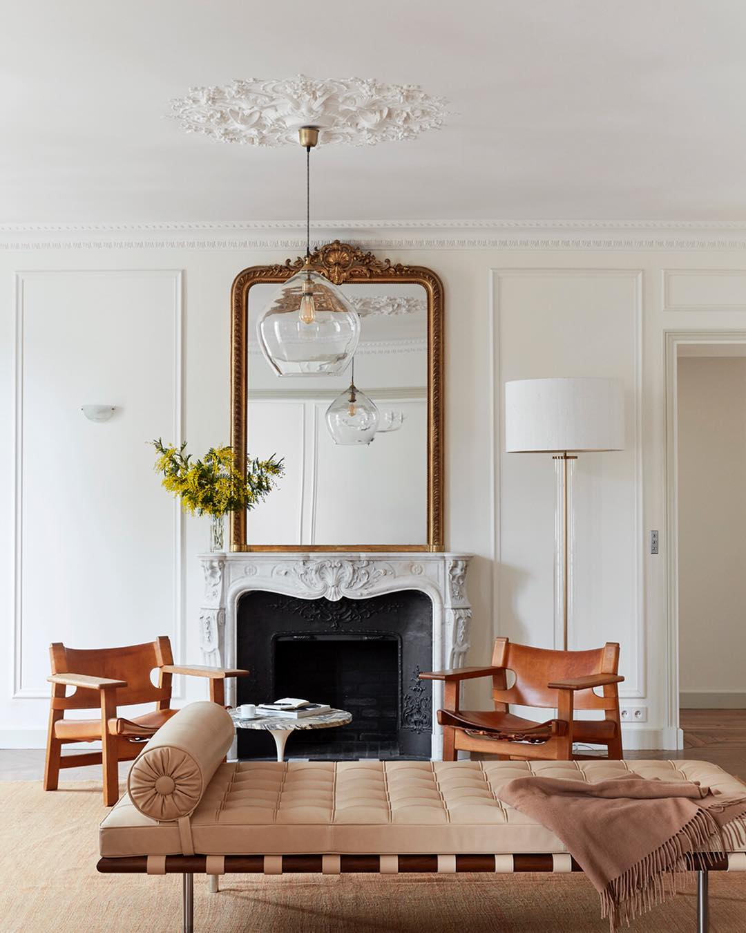 Parisian mirror in Paris apartment with fireplace and beige leather chairs via @abkasha
