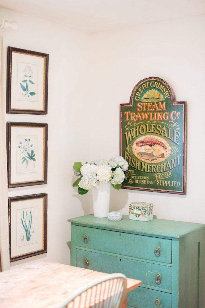 Vintage grocery store sign decor and turquoise cabinet via theeverygirl
