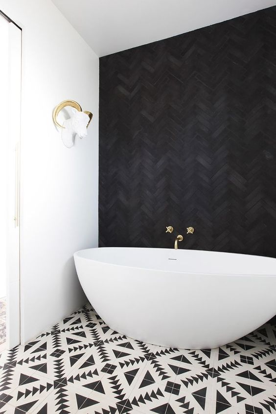 Bathroom with Black Herringbone Tile on wall with freestanding bathtub
