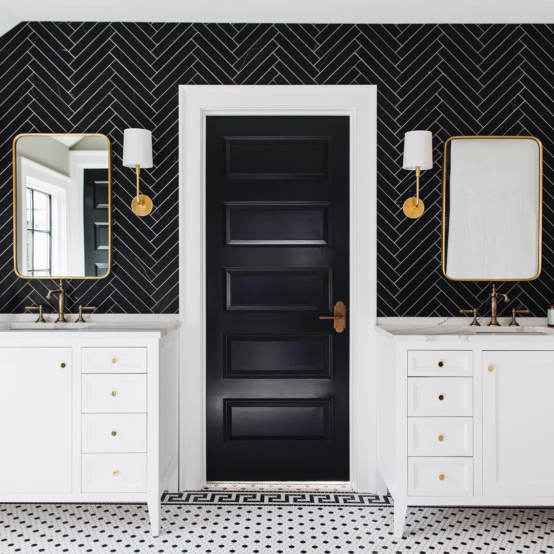 Bathroom with Double Vanity and Black Herringbone Tiles on wall and black door @stofferphotographyinteriors