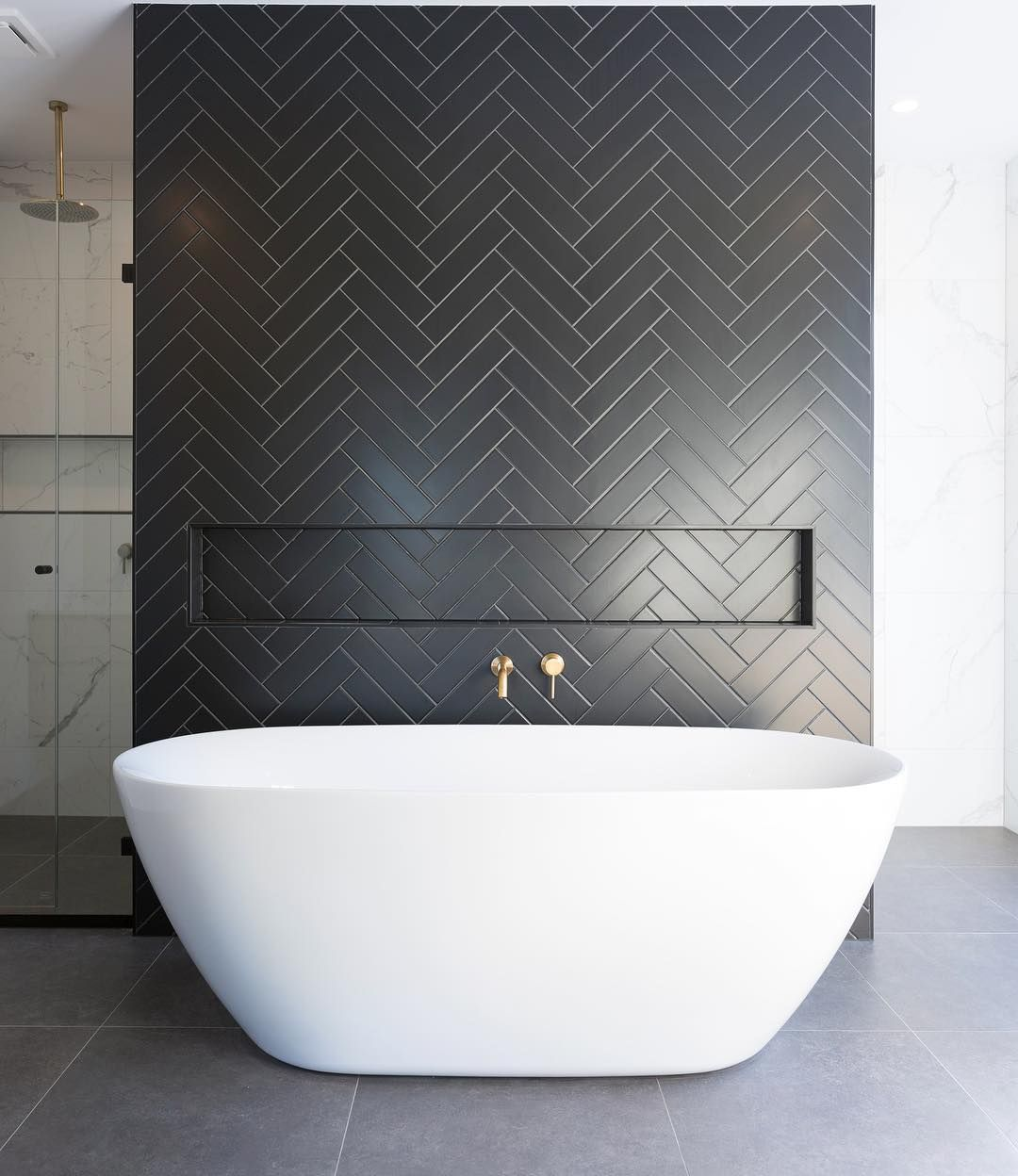 Bathrooms with Black Herringbone Tiles and white freestanding bathtub @turboconstructionau