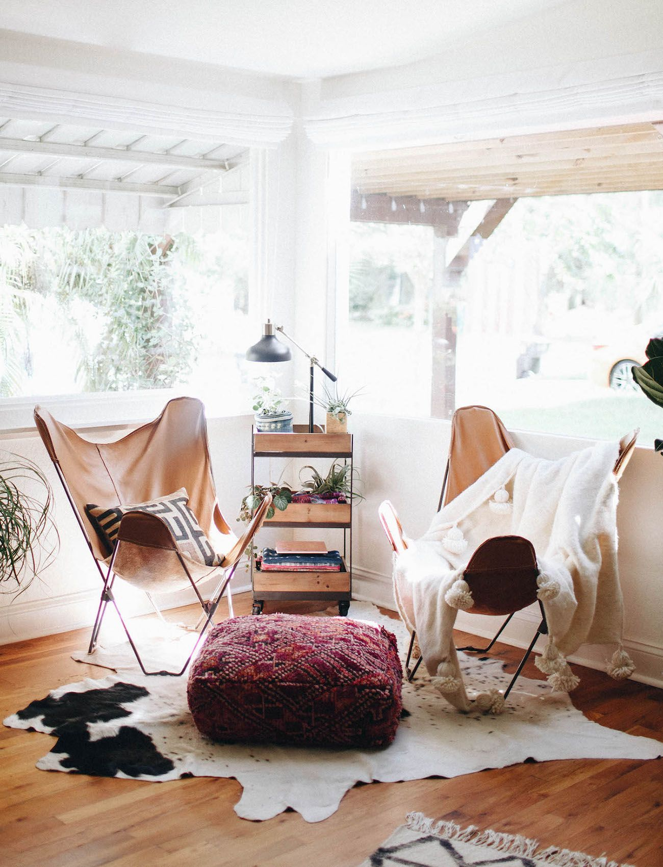 Boho seating - Leather butterfly chairs, a textile pouf ottoman, and fur throws