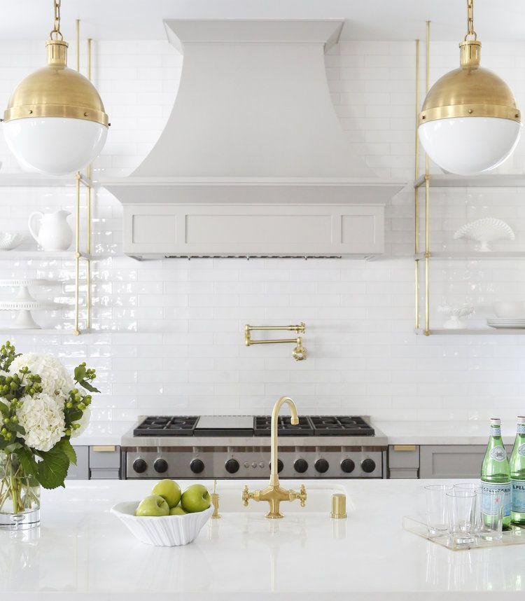 Brass Pendant Lights above white kitchen island via @sharontaftianinteriors