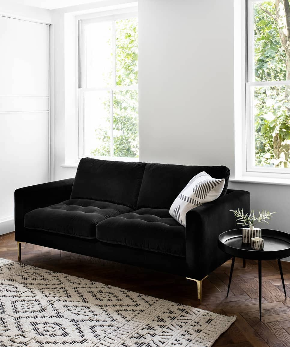 Modern black sofa in white living room via @heals_furniture