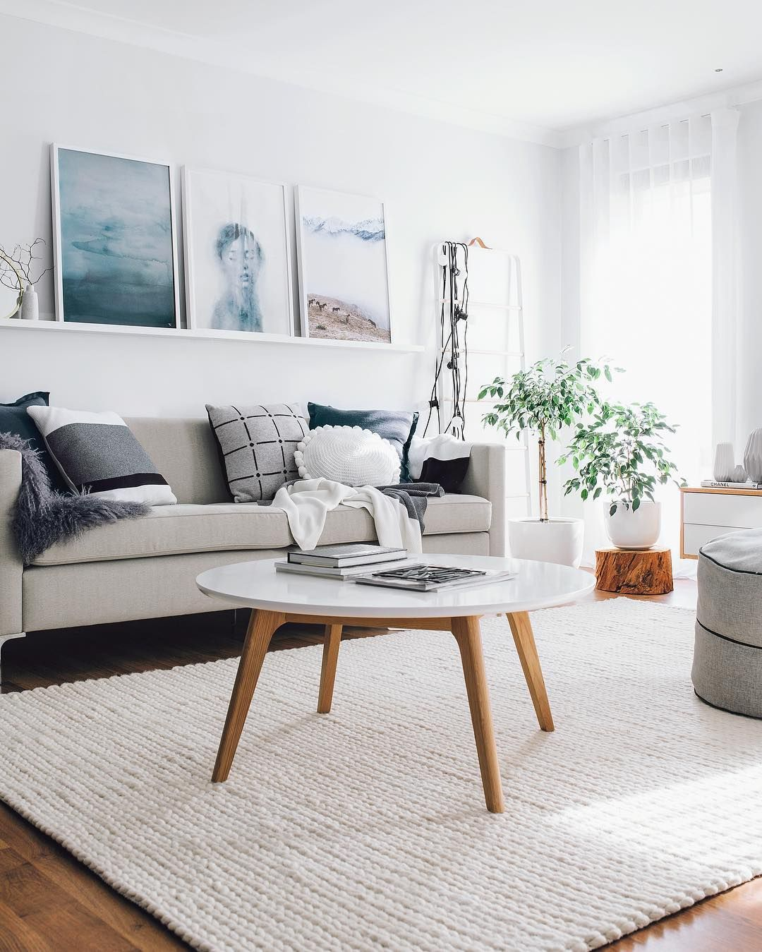 Off-white woven wool rug with a light gray sofa and a round white coffee table with wood legs