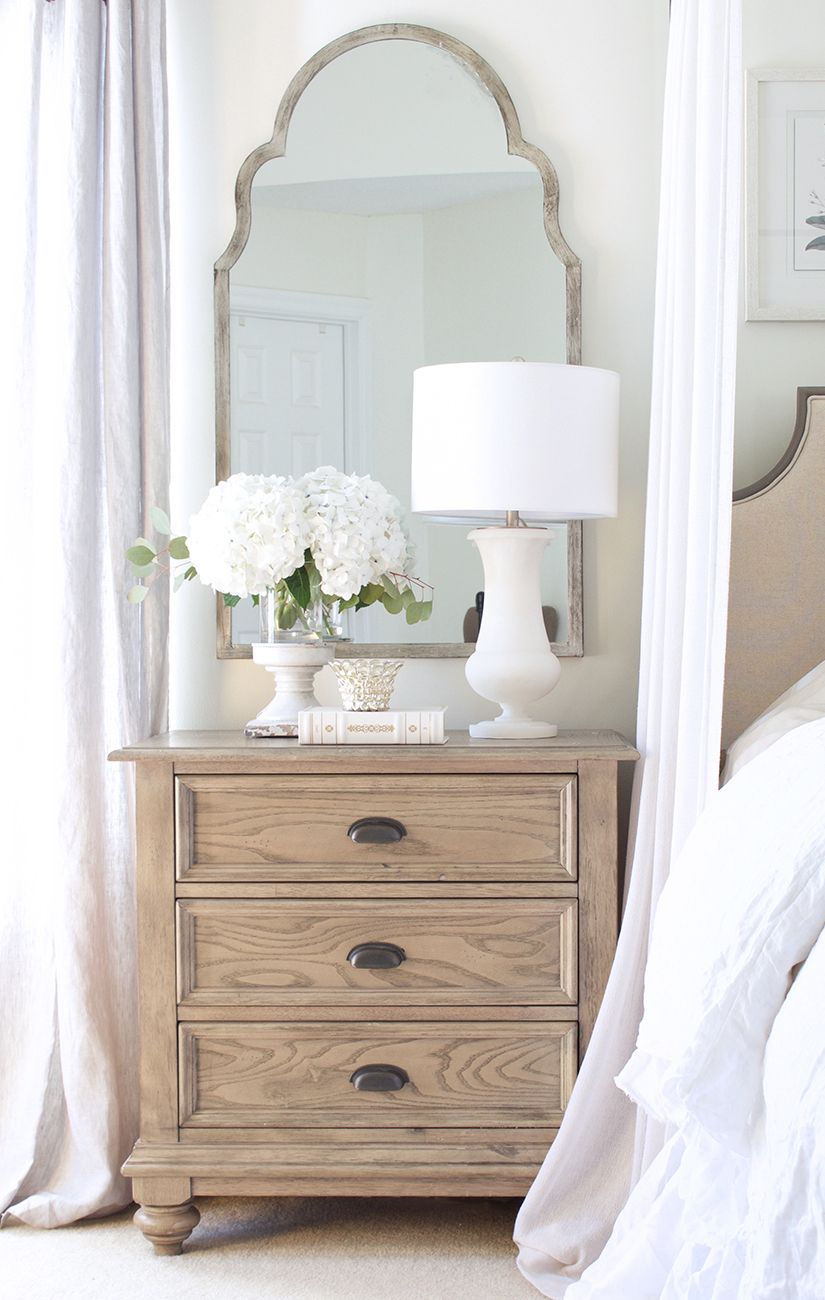 White Table Lamp on Wood Nightstand by Bed via tuftandtrim