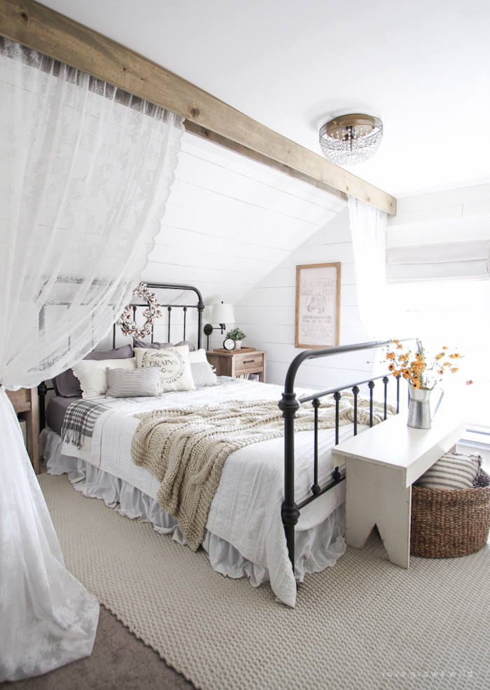 Farmhouse Bed with metal frame in room with wood ceiling beam via lovegrowswild