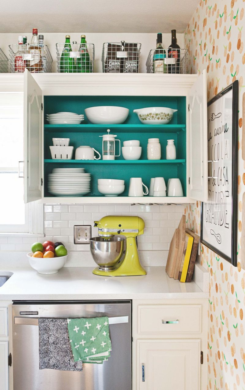 Colorful Kitchen Cabinet Organization with Wire Baskets on top via A Beautiful Mess