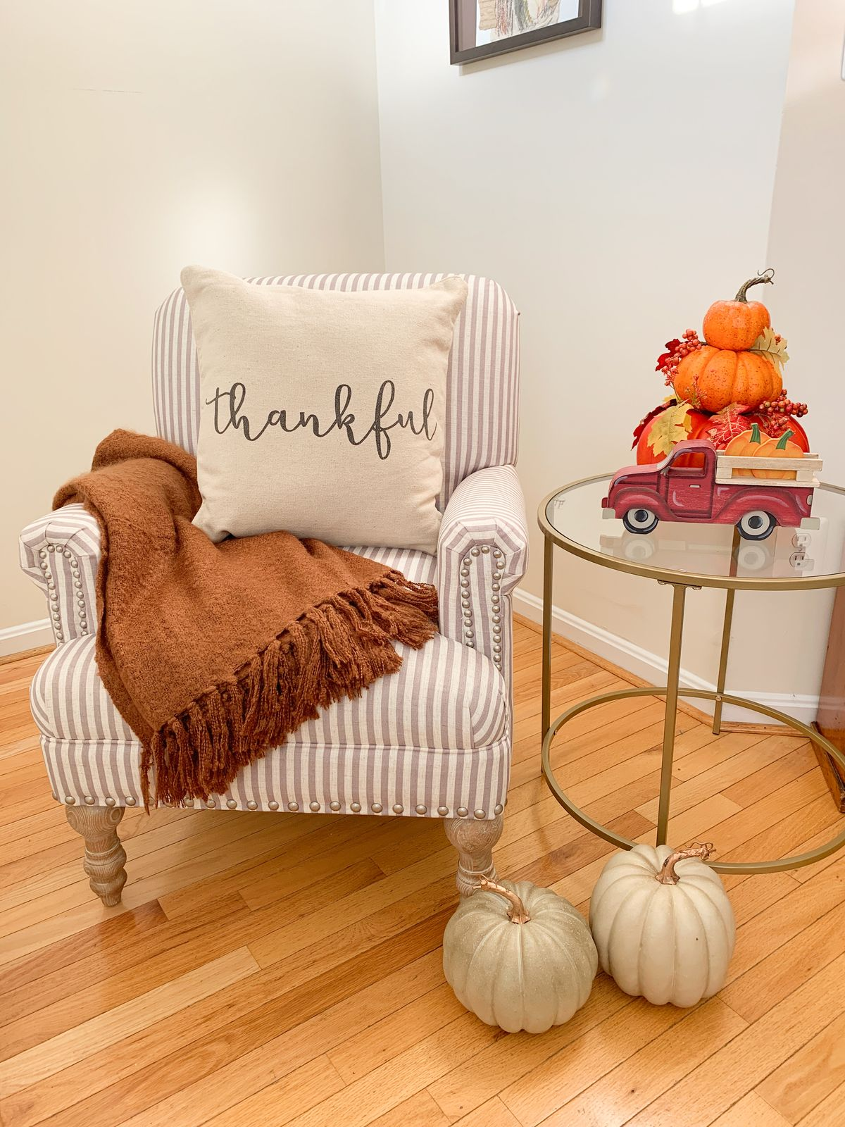 Cozy Fall Accent Chair Decor - Beige striped chair from Walmart, rust orange blanket, pumpkin decor and fall harvest truck decor