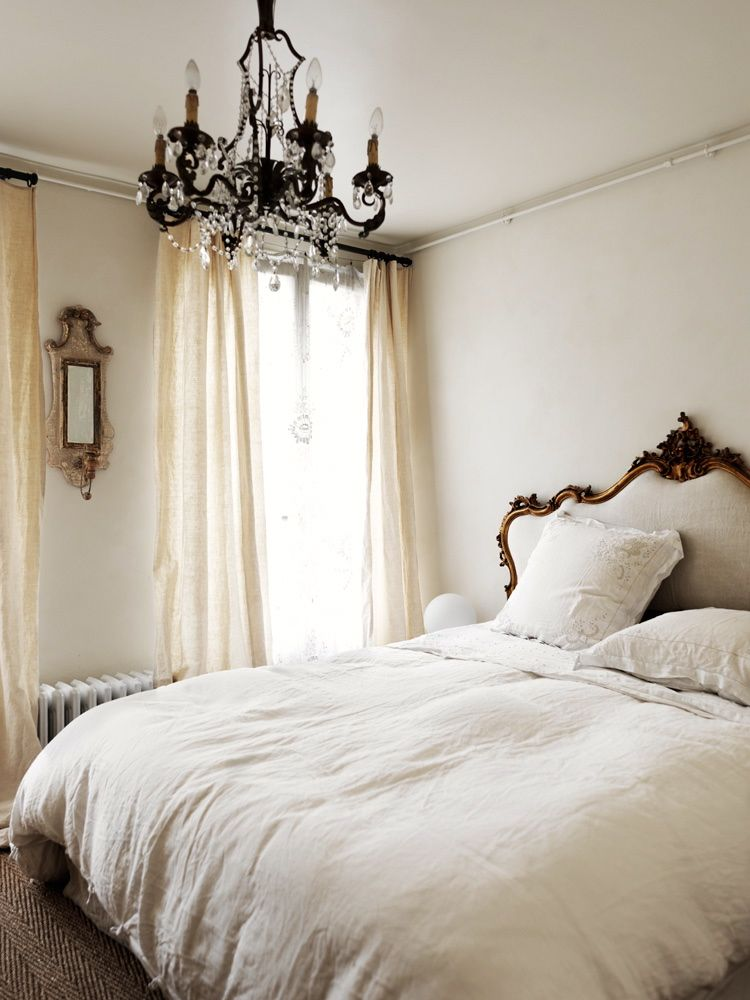 Parisian bedroom with French headboard and chandelier via Marianne Tiegen