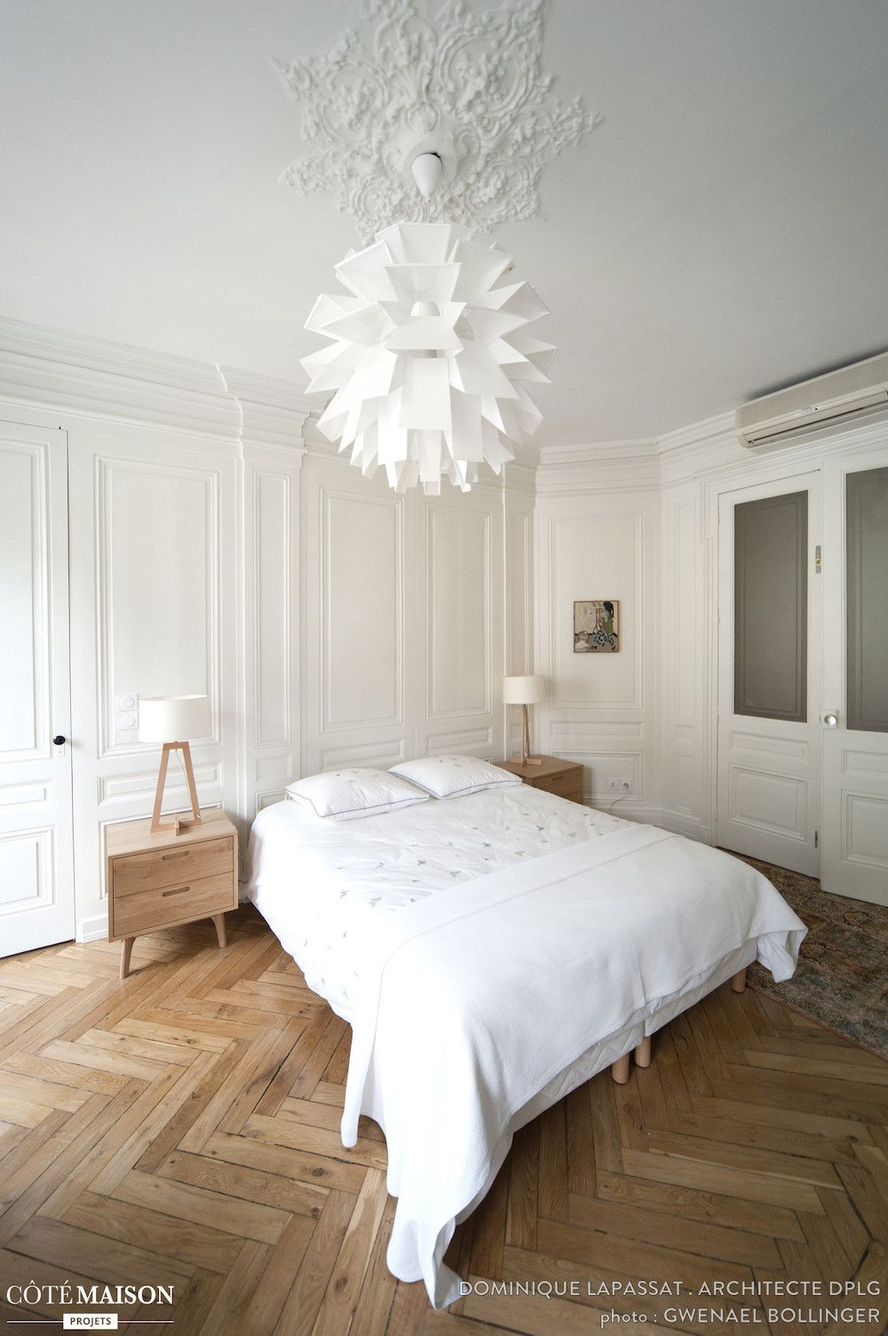 Parisian bedroom with Modern light fixture and herringbone wood floors via Dominique Lapassat