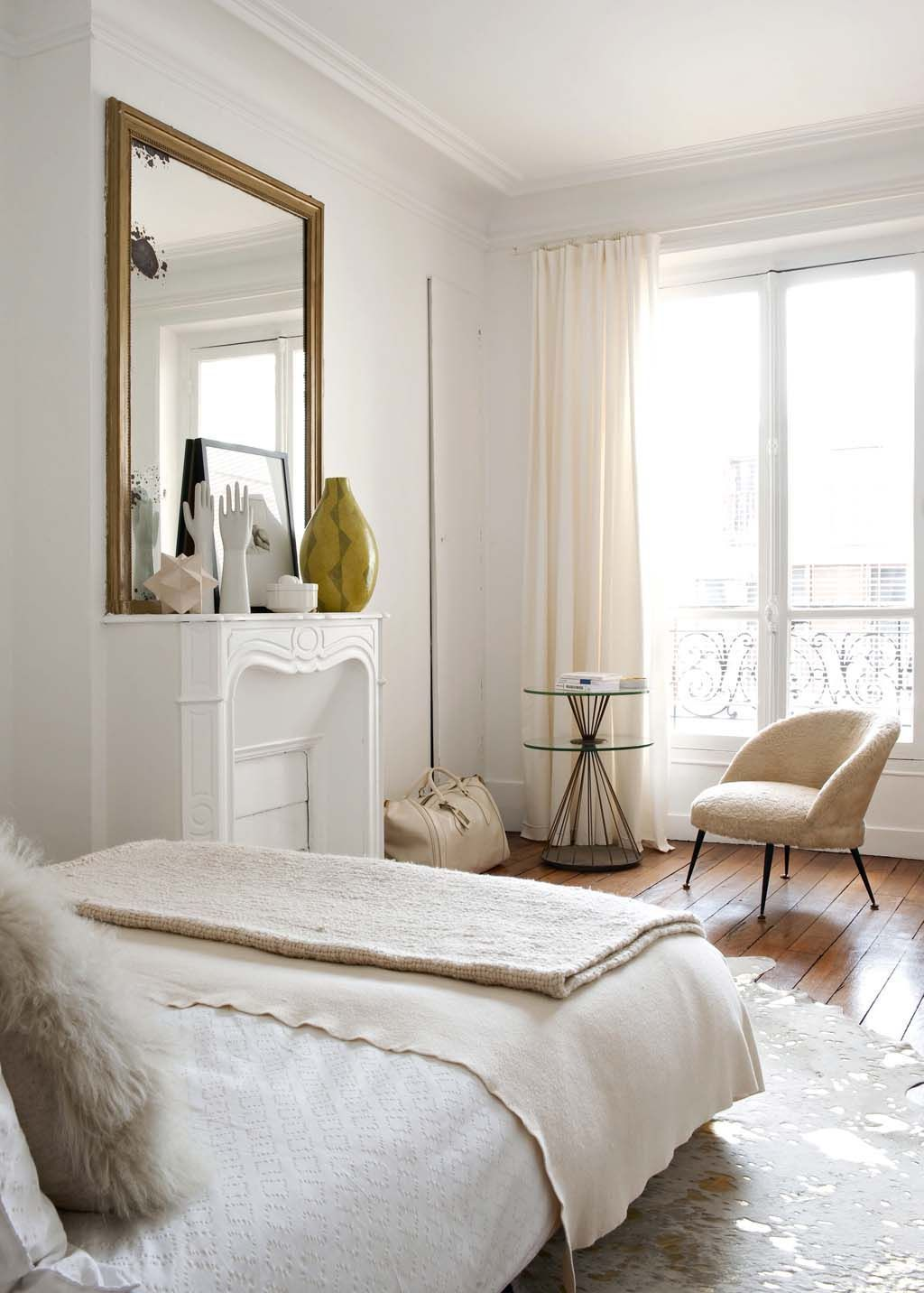 Parisian bedroom with beige accent chair via CoteMaison Emilie Bonaventure