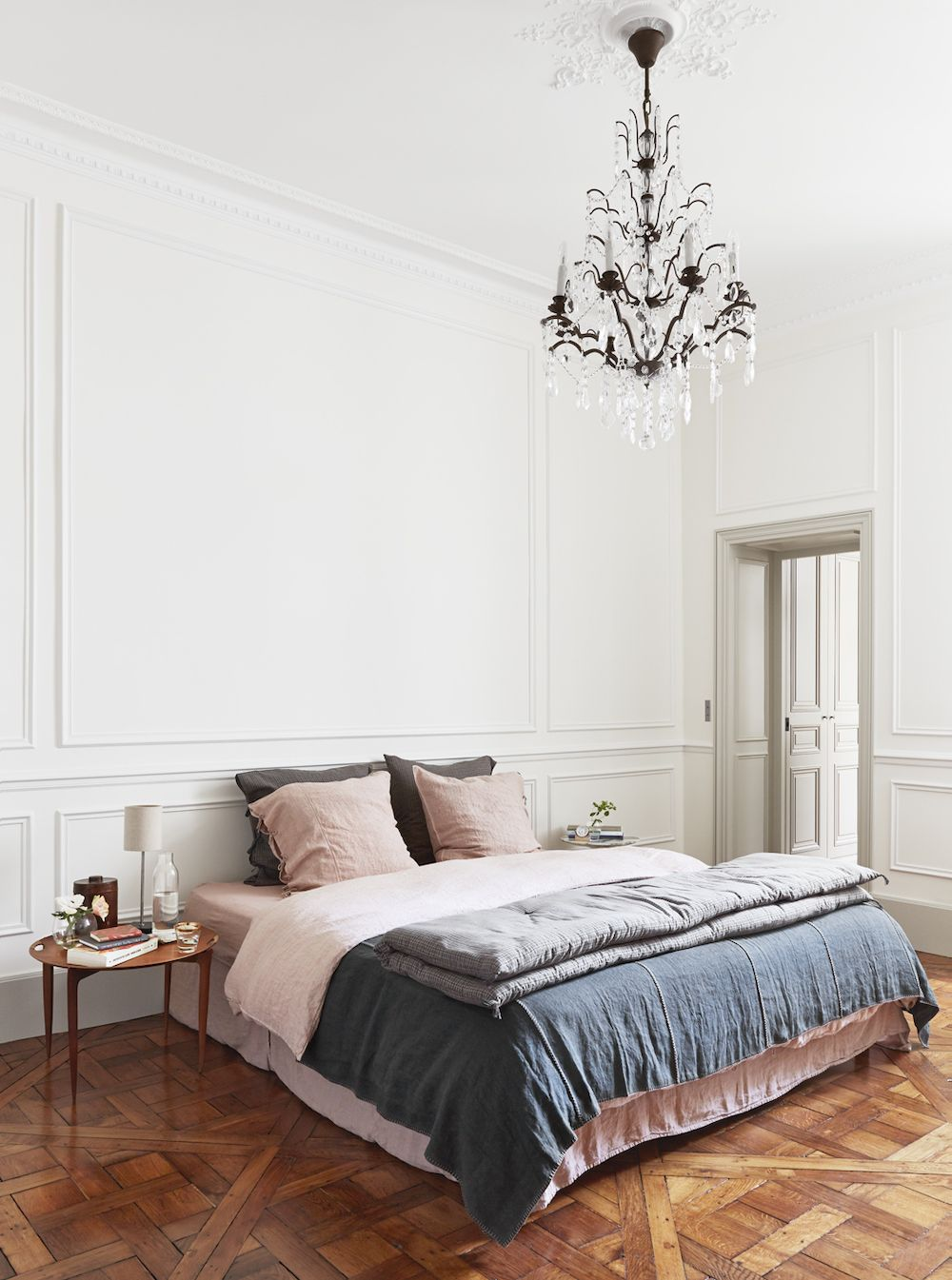 Parisian bedroom with faded linens and crystal chandelier via A + B Kasha