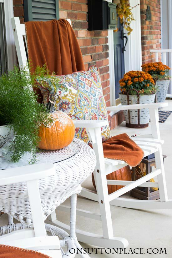 Fall front porch with orange throw blanket on a white rocking chair via onsuttonplace